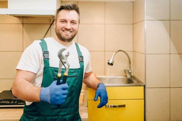 Klempner in uniform hält schraubenschlüssel, handwerker
