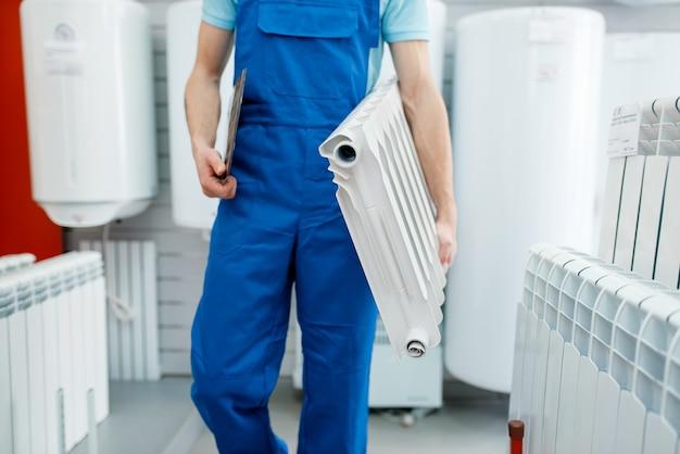 Klempner in uniform hält wasserheizkörper im klempnergeschäft. mann kauft sanitärtechnik im shop