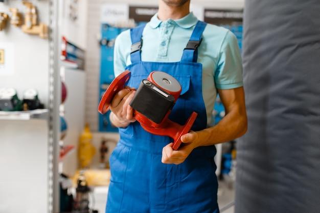 Klempner in uniform hält wasserpumpe am schaufenster im klempnergeschäft. mann kauft sanitärtechnik im shop