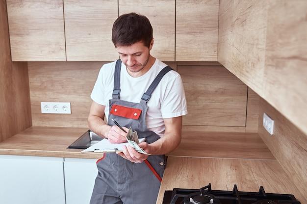 Klempner in uniform unterzeichnet einen vertrag für dienstleistungen in der küche