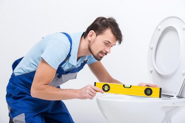 Klempner mit der gebäudeebene während der arbeit.