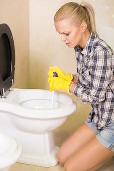 Klempner mit gummikolben in einem badezimmer. reinigungskonzept