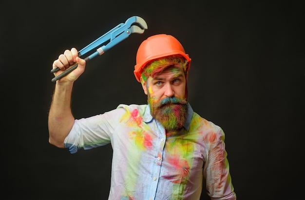 Klempner mit rohrzange oder klempnerschlüssel bärtiger mann im schutzhelm mit reparaturwerkzeugen