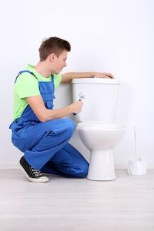 Klempner mit toilettenkolben auf hellem hintergrund