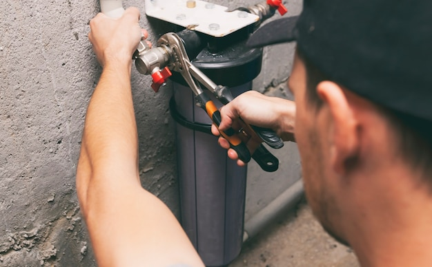 Klempner repariert wasserfilter im keller