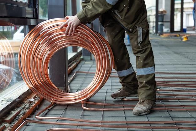 Klempner verlegt kupferrohre mit warmer heizung auf den boden
