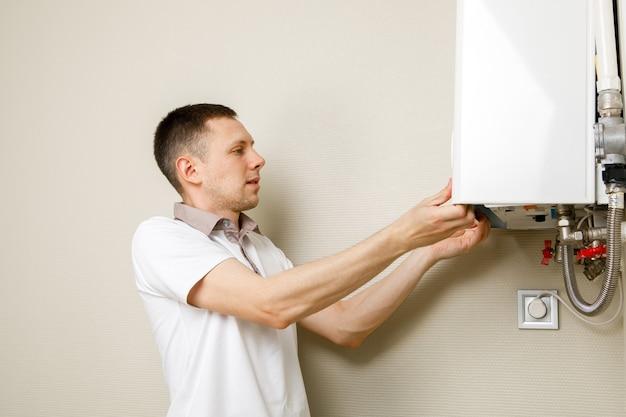 Klempner versucht, das problem mit der wohnungsheizung zu beheben. reparatur eines gaskessels