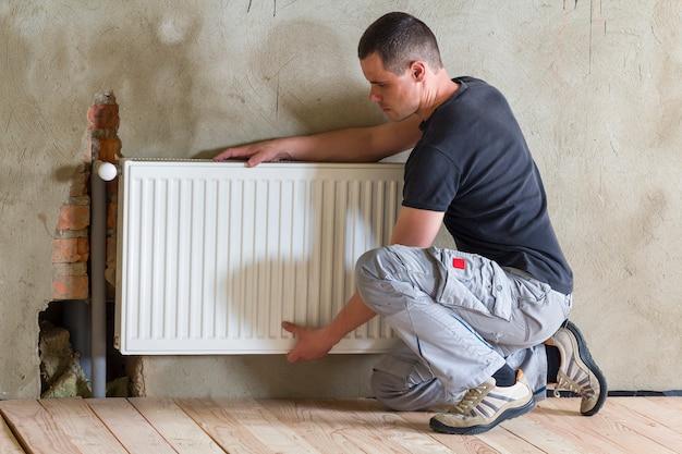 Klempnerarbeiter, der heizkörper in einem leeren raum einer neu gebauten wohnung oder eines neu gebauten hauses installiert.