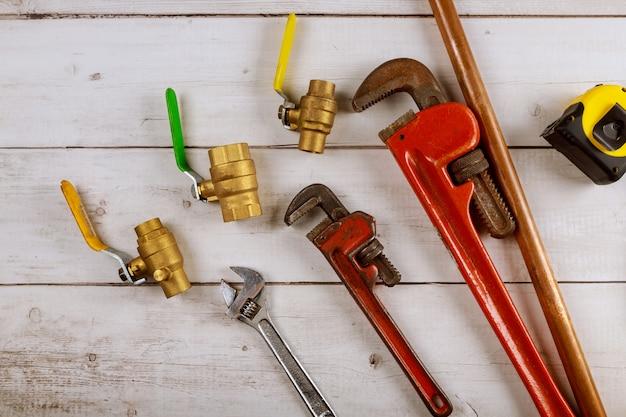 Klempnerarbeittor-kugelhähne, befestigungen am schraubenschlüssel und maßband auf holzbrett