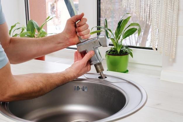 Klempnerhände entfernen den alten wasserhahn aus dem spülbecken