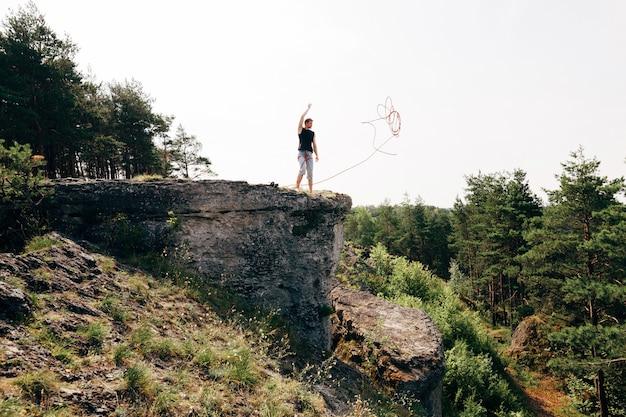 Kletterer, der am rand der klippe mit einem seil steht