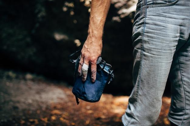 Kletterer, der pulverkreidemagnesium an seinen händen vor dem klettern aufträgt