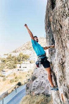 Kletterer heben arm auf felsen