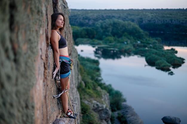 Kletterer überwindet anspruchsvolle kletterroute. ein mädchen klettert auf einen felsen.