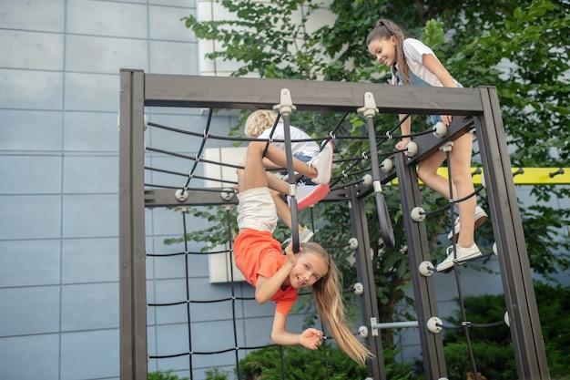 Klettern. kinder klettern auf spielplatz im freien und sehen aufgeregt aus
