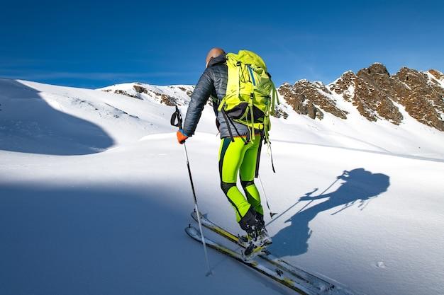 Klettern sie mit skiern und robbenfellen im neuschnee.