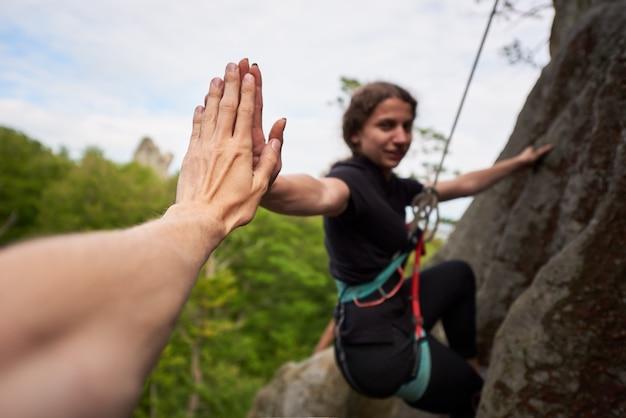 Kletternder überhängender felsen des kletterers mit seil. klettern der helfenden frau des mannes. händchen halten.