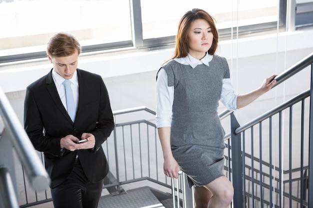 Kletterndes treppenhaus des geschäftsmannes und der geschäftsfrau im büro