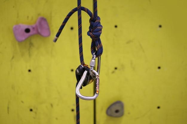 Klettersimulatorhaken, karabinerhaken mit kletterseil und gelbe wand