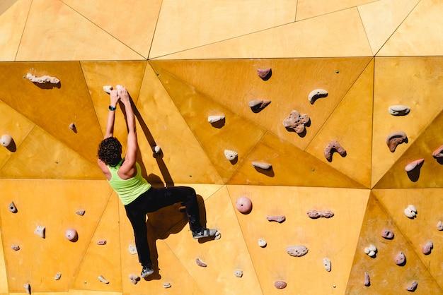 Kletterwand mit einem erfahrenen bergsteiger, der draußen riskante übung mit freiheit durchführt.