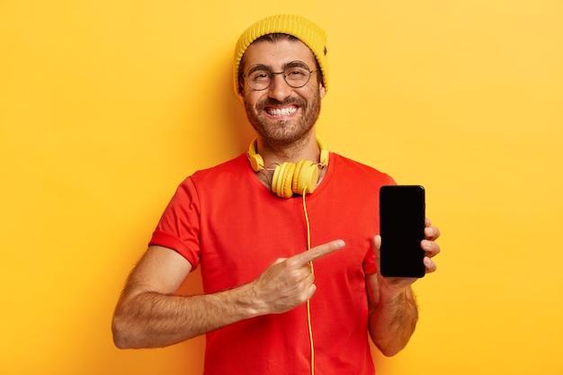 Klicken sie auf diese schaltfläche. erfreut zufriedener männlicher student in trendigem hut und rotem t-shirt, zeigt mit zeigefinger auf smartphone-gerät