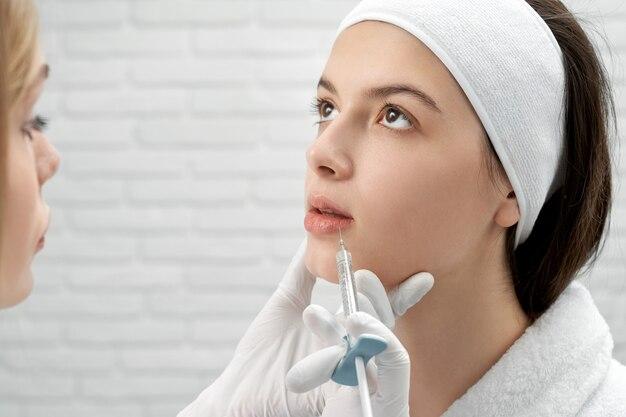 Klient, der kosmetikerin besucht und gesichtsspritzen tut
