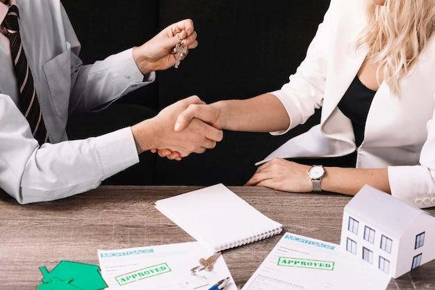 Klient und mittel, die hände im büro rütteln