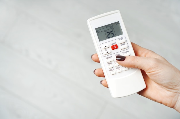 Klimaanlage fernbedienung in weiblichen händen
