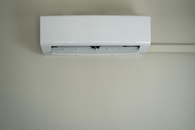 Klimaanlage innen oben der raummann, der die fernbedienung der offenen klimaanlage bedient, spart energie