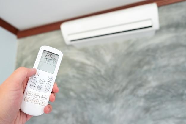Klimaanlage innerhalb des raumes mit der frau, die fernsteuerpult laufen lässt oder schließt