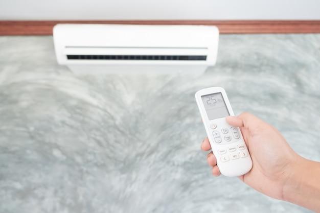Klimaanlage innerhalb des raumes mit der frau, die fernsteuerpult laufen lässt oder schließt.