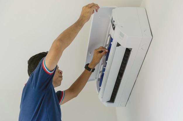 Klimaanlagenreparaturen in der blauen uniform überprüfen und reparieren die luft, die an der wand hängt.