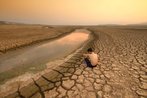 Klimawandel junger mann sitzt in der nähe des trocknenden flusses