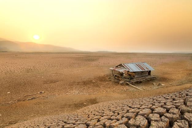 Klimawandel trockener see und hausfloß auf rissiger erde