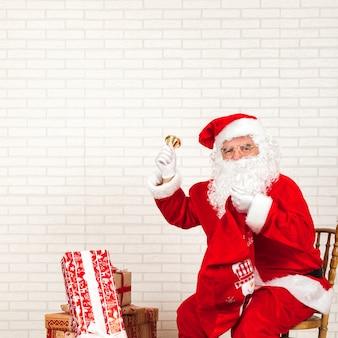 Klingelglocke des weihnachtsmanns, die auf stuhl sitzt