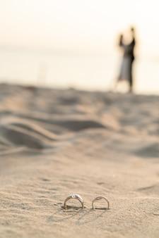 Klingelt am strand mit braut und bräutigam