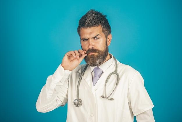 Klinikmedizinberuf und leutekonzept ernster bärtiger arzt mit stethoskop in