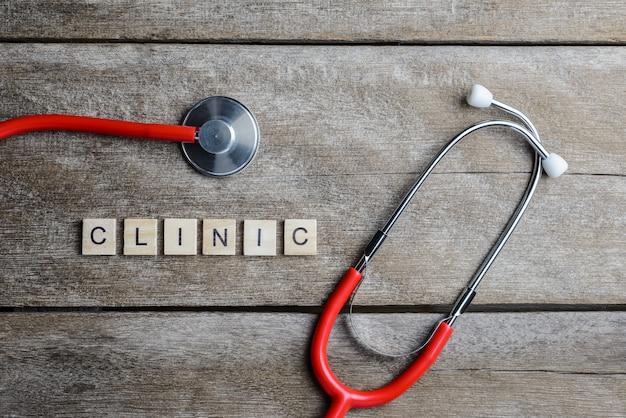 Kliniktextwort gemacht mit hölzernen blöcken und rotem herzen, stethoskop auf holztisch