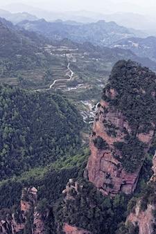 Klippe neben einem berg mit bäumen und vegetation bedeckt