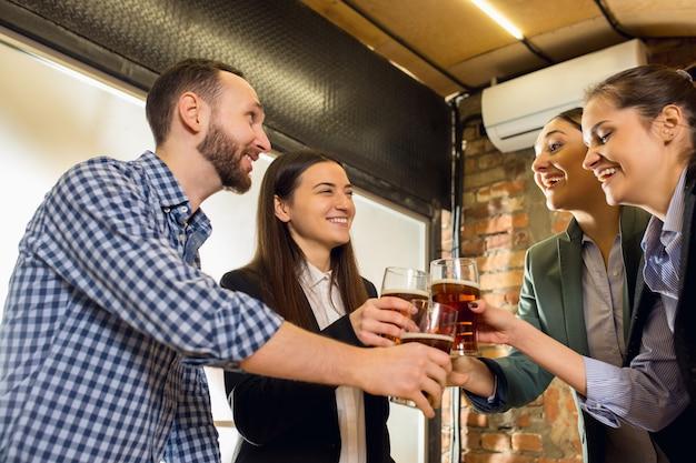 Klirren. fröhliche mitarbeiter, die nach einem angespannten arbeitstag ein firmenevent feiern. schauen sie erfreut, freundlich, fröhlich. bier trinken. konzept der bürokultur, teamwork, freundschaft, urlaub, wochenende.