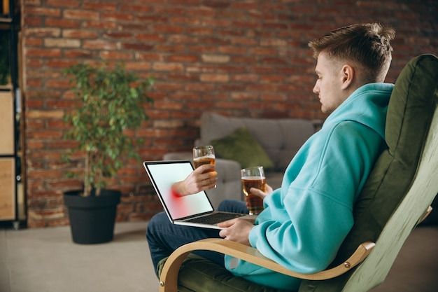 Klirren. junger mann, der bier beim treffen freunde auf virtuellem videoanruf trinkt. online-ferngespräch, zu hause auf einem laptop chatten. konzept für sichere remote-meetings und unterhaltung.