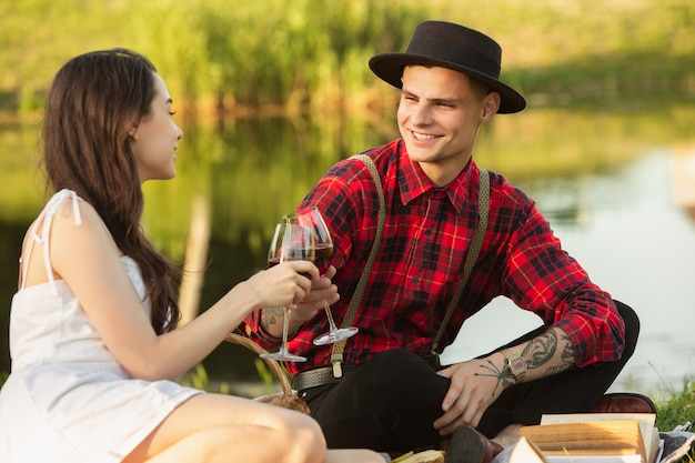 Klirrende gläser. kaukasisches junges, glückliches paar, das am sommertag zusammen ein wochenende im park genießt.