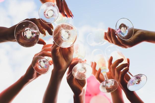 Klirrende gläser mit alkohol und toasten, party. herzlichen glückwunsch zur veranstaltung. fröhliche partyfreunde.