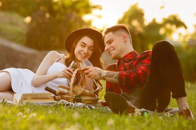 Klirrende gläser mit wein. kaukasisches junges paar, das am sommertag ein wochenende im park genießt?