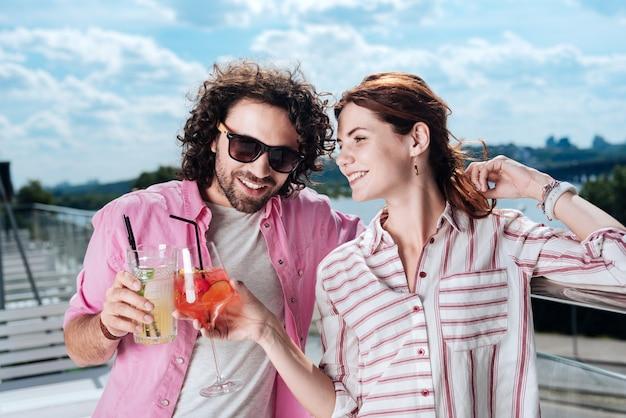 Klirrende gläser. strahlend lächelnde frau, die ihr glas mit ihrem mann klappert, während erfrischende sommercocktails genießen