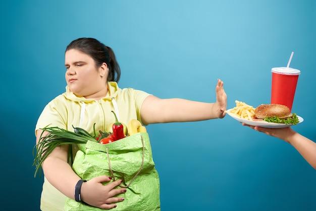 Klobiges brünettes mädchen mit geschlossenen augen, das paket mit obst und gemüse hält und zeichenstopp durch ihre hand zum fastfood auf dem teller zeigt. konzept der ablehnung von junk food zugunsten einer gesunden mahlzeit