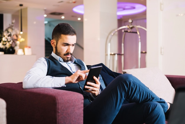 Klopfende tablette des jungen eleganten mannes
