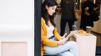 Klopfender Tablettenschirm der Frau, der im Café sitzt