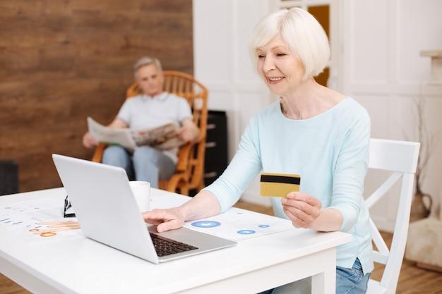 Kluge, kluge ältere frau, die einen großartigen gegenstand im internierten findet und mit ihrer kreditkarte einen kauf tätigt