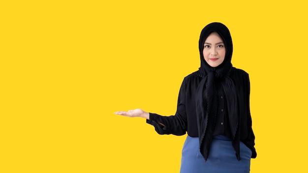 Kluge und schöne muslimische frau, die auf leuchtend gelber wand aufwirft